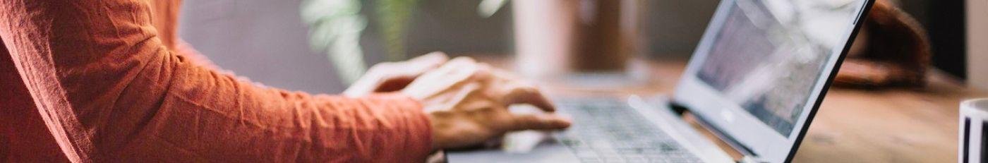 Estudiante tecleando en el portátil durante las clases en línea