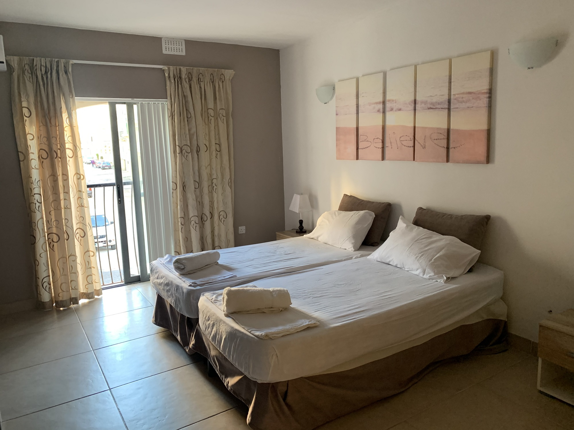A twin room with a balcony at BELS Gozo student residence
